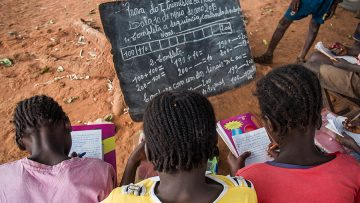 Bie, Angola - May 10, 2013. Three girls undertake a maths exam by a tree in a rural school. Access to education in low income countries of sub-saharan Africa is one of the challenges of the global community, as stated in the Sustainable Development Goals.
