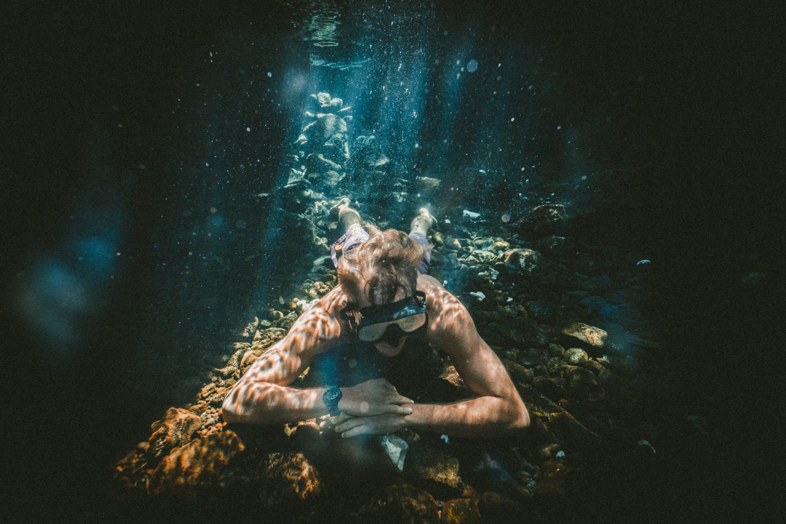 man zit op bodem oceaan